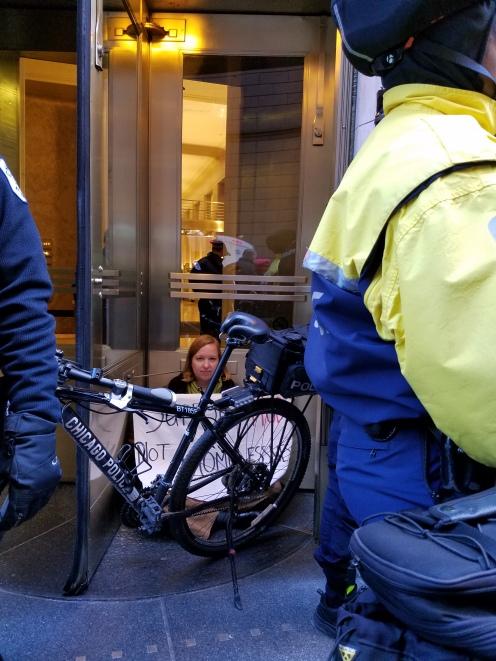 Protester blocking revolving door at BOA Financial Center